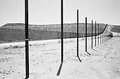 Naco, Arizona<br /> May 4, 2008<br /> <br /> East of Naco new border fencing marks the US/Mexican border. The vast majority of the Arizona/Mexican border is now marked by vehicle barrier or high fencing.<br /> <br /> In the foreground the unfinished million-dollar fence that was to be constructed by the MinuteMen two years ago remains incomplete. They collected the funds from private citizens but never completed the fence. However the US government has.