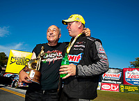 Sep 15, 2019; Mohnton, PA, USA; NHRA pro stock driver Fernando Cuadra (left) holds the trophy won by Jason Line during the Reading Nationals at Maple Grove Raceway. Mandatory Credit: Mark J. Rebilas-USA TODAY Sports