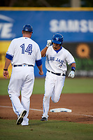 Dunedin Blue Jays first baseman Max Pentecost (10) is congratulated by manager John Schneider (14) as he rounds third base after hitting a home run in the bottom of the fifth inning during a game against the St. Lucie Mets on April 20, 2017 at Florida Auto Exchange Stadium in Dunedin, Florida.  Dunedin defeated St. Lucie 6-4.  (Mike Janes/Four Seam Images)
