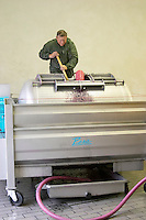 Domaine Haut-Lirou in St Jean de Cuculles. The Pic St Loup mountain top peak. Pic St Loup. Languedoc. Wine press. Winery worker filling the press. France. Europe.