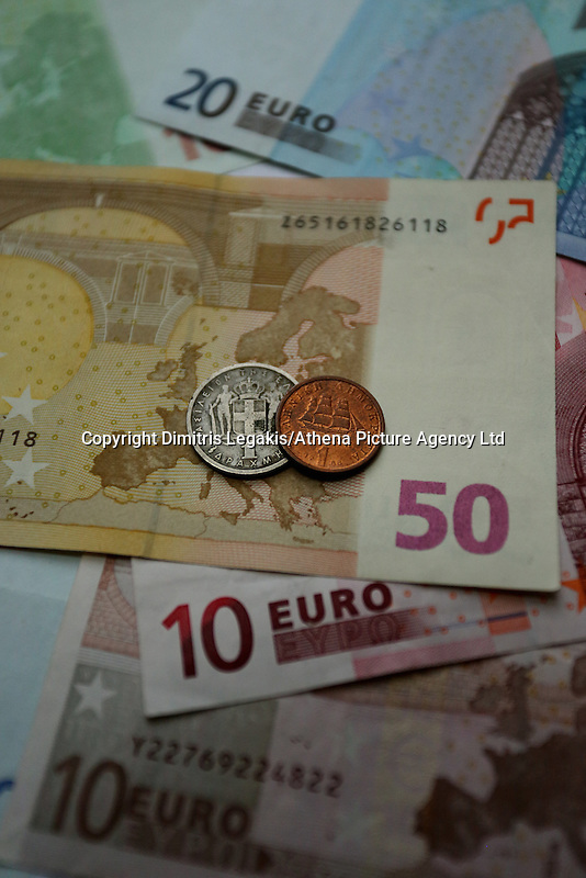Two old drachma coins from different periods on euro paper notes