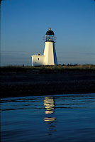 Calm waves reflect the Prudence Island Lighthouse at sunset