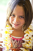 Young girl wearing a fragrant plumeria lei