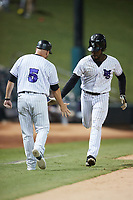 Jeremiah Burks (4) of the Winston-Salem Dash slaps hands with third base coach Ryan Newman (5) after hitting a home run against the Bowling Green Hot Rods at Truist Stadium on September 9, 2021 in Winston-Salem, North Carolina. (Brian Westerholt/Four Seam Images)