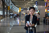 Happy businesswoman reading text message on mobile phone in the terminal at the Austin International Airport.