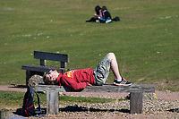 CARDIFF, UK. 2nd April 2017. A man relaxes on a bench in sunny weather in Cardiff Bay