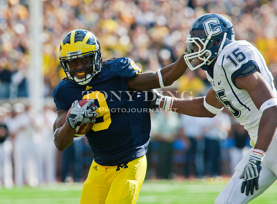 Michigan wide receiver Martavious Odoms (9) stiff arm Connecticut safety Jerome Junior (15) in the second quarter of an NCAA college football game, Saturday, Sept. 4, 2010, in Ann Arbor, Mich. (AP Photo/Tony Ding)