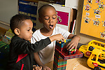Preschool 4 year olds two boys playing with small vehicles on top of contruction they made from magnetic blocks