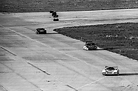 #00 March 83G of Sarel van der Merwe, Graham Duxbury, and Tony Martin, 43rd place, #6 Porsche 935 of Derek Bell, A.J. Foyt, and Bob Wollek, and #99 Chevrolet Corvette, of Phil Currin, Steve Gentile, Jim Cook, and Tommy Morrison, 35th place, aerial view from Goodyear blimp, 3rd place,  12 Hours of Sebring, IMSA Camel GT race, Sebring International Raceway, Sebring, Florida, March 24, 1984.  (Photo by Brian Cleary/www.bcpix.com)