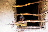 Lolgorian, Kenya. Young African girl at the window of her house with rough wooden bars across it.