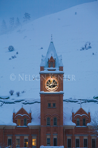 The lighted clock on Main Hall in early morning on the University of Montana campus in Missoula, Montana