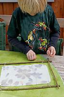 Kinder basteln ein Fensterbild mit Blüten, Junge verknotet mit Schnur das Pergamentpapier mit dem Holzrahmen