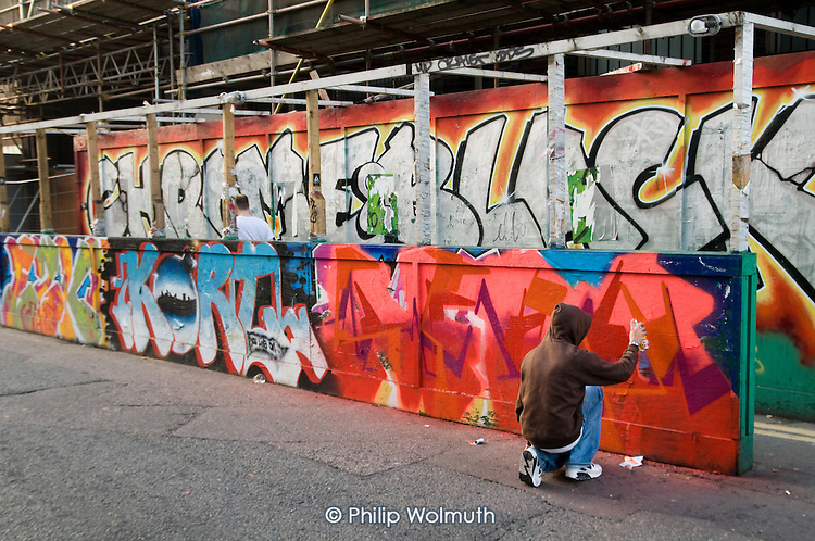 A young man with a spray-can paints on a temporary builder's hoarding in Shoreditch, London.