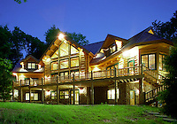 The rear exterior of an executive style log home, with lights on in the evening.