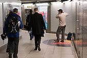 A flautist performs to commuters at an authorised busking spot in Westminster underground station.
