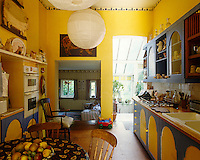 This country-style yellow-painted kitchen extends through to a conservatory on the right and a playroom on the left