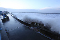 """Pictured: Huge waves crashing against the promenade wall by a sign reading """"Bathing Dangerous"""" in Porthcawl, south Wales. Friday 03 January 2014<br /> Re: Flood warnings have been issued  by the Environment Agency due to strong winds and high tides for part of the UK."""