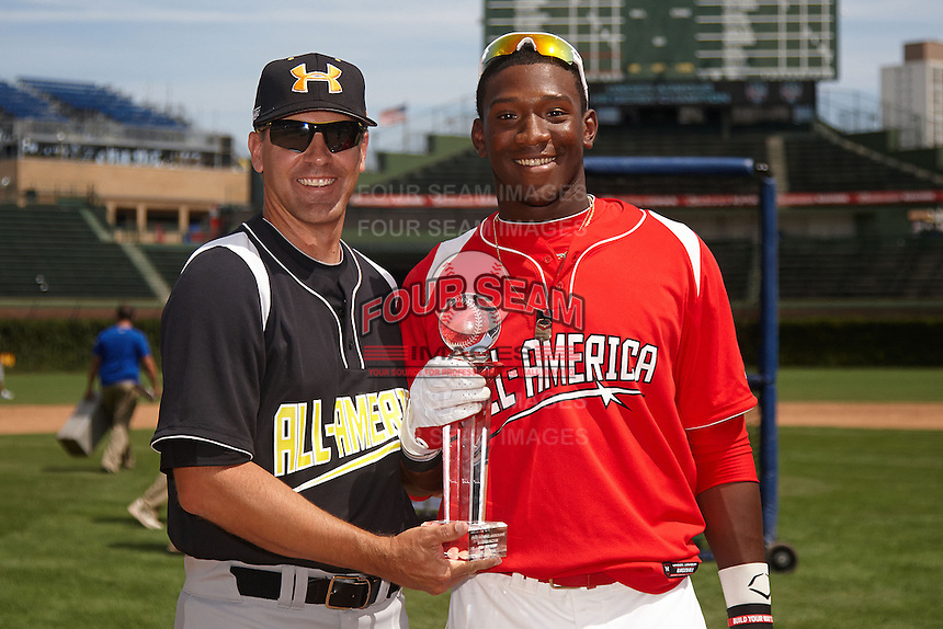 Outfielder Justin Williams #4 of Terrebonne High School in Houma, Louisiana gets the home run derby trophy from Steve Bernhardt while participating in the Under Armour All-American Game powered by Baseball Factory at Wrigley Field on August 18, 2012 in Chicago, Illinois.  (Mike Janes/Four Seam Images)