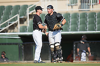 Kannapolis Intimidators relief pitcher Ian Hamilton (12) shakes hands with catcher Nate Nolan (24) after closing out the win over the Greensboro Grasshoppers at Intimidators Stadium on July 17, 2016 in Greensboro, North Carolina.  The Intimidators defeated the Grasshoppers 3-2 in game one of a double-header.  (Brian Westerholt/Four Seam Images)