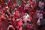 Visitors and devotees are greeted by coloured water from the roof of the temple by the locals at Krishna temple at Nandgaon 5 kms away from Barsana on the 2nd day of lathmar holi, Uttar Pradesh, India . Lathmar holi is celibrated 7 days before the actual holi day.