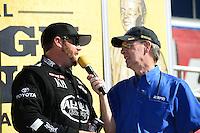 Nov. 11, 2012; Pomona, CA, USA: NHRA top fuel dragster driver Shawn Langdon (left) talks with NHRA announcer Bob Frey during the Auto Club Finals at at Auto Club Raceway at Pomona. Mandatory Credit: Mark J. Rebilas-