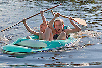 Brother and sister laughing and paddling in an inner tube on a lake together