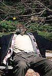 HOMELESS MAN RELAXES ON BENCH IN MANHATTAN PARK