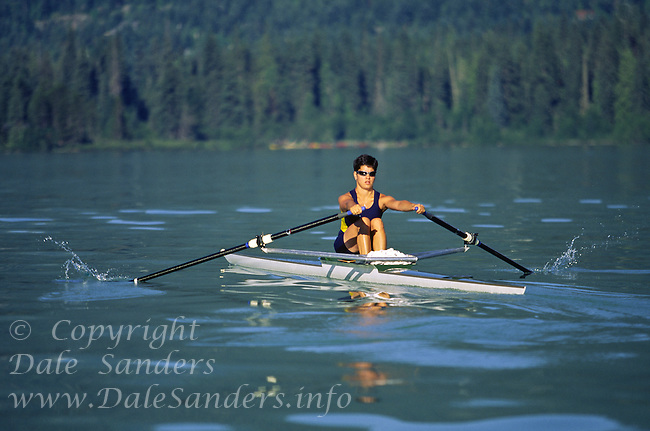 A woman rowing or sculling a single shell on Green Lake, Whistler, British Columbia, Canada.