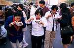 China Beijing 1990s. Chinese family friends eating traditional fast market stall food with chop sticks 1998