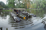 Historic 1963 APGP amphibious Land Rover with flotation bags swimming in a lake to commemorate Land Rovers 50th anniversary at the 1998 Belgium National show.  RELEASES MAY BE AVAILABLE FOR CERTAIN USES, PLEASE ENQUIRE. Automotive trademarks are the property of the trademark holder, authorization may be needed for some uses. --- Info: This Land Rover is known as the A.P.G.P. , Air Portable General Purpose. Based around a 1 Ton military spec 109 24 Volt, it has amphibious capabilities. This LR floats! A small propeller is mounted on te rear propshaft, the air bags were inflated from the exhaust. This was to be a multi role vehicle. The APGP can be a radio station, wombat carrier or 110 Volt power tool source and could be stacked two high for air transport. About 26 of these vehicles were built for troop trials in 1964 but never entered service. This is the first vehicle to find its way into the Dunsfold Collection, purchased by Brian Bashall in 1968 via Ruddington military auctions. In 1998 for the 50th Anniversary of Land Rover Brians son, Philipp Bashall, had the mad idea to swim the APGP, which turned out to be an interesting challange as the flotation bags were by then already over 30 years old. Steering in the water is interesting as it relies on the front tyres as rudders, wind could be disastrous.