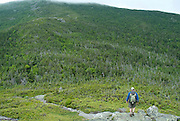 A hiker ascending the Howker Ridge Trail during the summer months in the Presidential Range of the White Mountains, New Hampshire USA