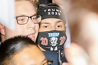 """A man wears a facemask and headband reading """"Trump 2020"""" as he stands behind the stage barricade as Eric Trump, son of US president Donald Trump, greets people and signs MAGA hats and Trump campaign signs after speaking during a Make America Great Again! campaign rally at the DoubleTree by Hilton Manchester Downtown in Manchester, New Hampshire, on Mon., Oct. 19, 2020."""