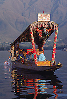 INDIAN TOURISTS take a ride in a SHIKARA, local paddle boat with a canopy, on DAL LAKE in SRINIGAR - KASHMIR, INDIA