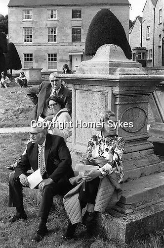 Painswick Clypping church service Gloucestershire Uk 1973. Parents, visitors sit and watch amongst the tomb stones. 1970s UK