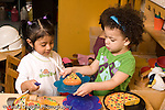 Education Preschool 3-4 year olds pretend play in kitchen area two girls interacting playing with food and dishes horizontal