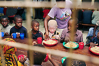 An albino child sits down to eat with other children at his boarding school in Dar Es Salaam. Discrimination against albinos is a serious problem throughout sub-Saharan Africa, but recently in Tanzania albinos have been killed and mutilated, victims of a growing criminal trade in albino body parts fuelled by superstition and greed. Limbs, skin, hair, genitals and blood are believed by witch doctors to bring good luck, and are sold to clients for large sums of money, carrying with them the promise of instant wealth.