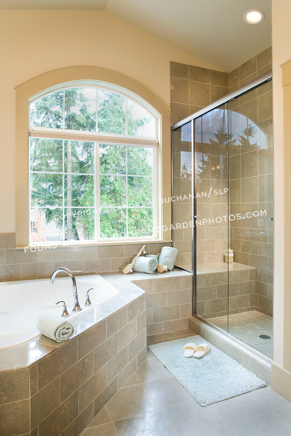 A roomy master bathroom suite with a raised deck corner tub, walk-in tiled shower with tiled bench seat, large window into the trees for plenty of natural light, and rolled towels and a loofa create an in-home spa feel in this contemporary spec home.