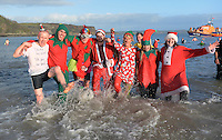 Pictured: People in Santa and elf costumes take to the freezing cold sea in Tenby, west Wales, UK. Monday 26 December 2016<br /> Re: Hundreds of people in fancy dress, take part in this year's music-themed charity event, the Boxing Day Swim in Tenby, Pembrokeshire, Wales, UK