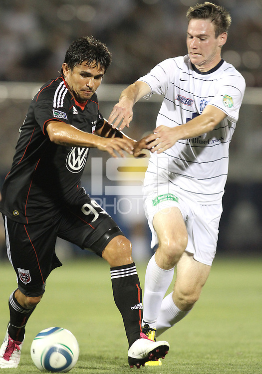Jaime Moreno #99 of D.C. United  is tackled by Tyler Ruthven #18 of the Harrisburg City Islanders during a US Open Cup match at the Maryland Soccerplex on July 21 2010, in Boyds, Maryland. United won 2-0.