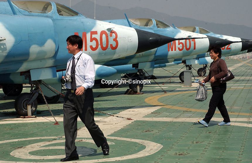 Tourists at a Chinese theme park called Minsk World in Shenzhen, China, pass a couple of MIG russian fighter planes..