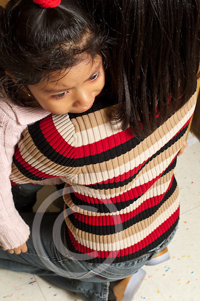 Education preschool 3-4 year olds vertical female teacher comforts sad girl separation