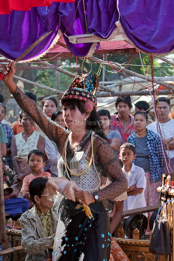 Myanmar, Burma. Bagan.  Dancer at a Nat Pwe Celebration, giving thanks for a year of good fortune.  The dancer has a knife in one hand and a dead, plucked chicken in the other.  A gift of money is pinned to her blouse.