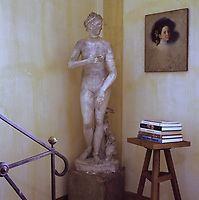 At the foot of the staircase leading to the attic master bedroom stands the sculpture of a woman beside an unfinished portrait of a young girl