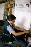 Woman weaving a carpet on a loom at a Tibetan Refugee Camp, Ladakh, Leh, India.