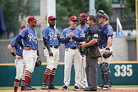 Frisco RoughRiders manager Joe Mikulik (25) talks with umpire Jose Matamoros while making a pitching change during a Texas League game against the Midland RockHounds on May 21, 2019 at Dr Pepper Ballpark in Frisco, Texas.  Andretty Cordero (4), Charlie Leblanc, Michael De Leon, Juremi Profar, and catcher Alex Kowalczyk (27) look on.  (Mike Augustin/Four Seam Images)