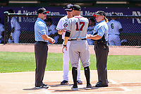 Quad Cities River Bandits manager Mickey Storey (17) and Kane County Cougars manager Blake Lalli (15) exchange lineup cards with umpires Jennifer Pawol and Jake Bruner prior to a Midwest League game against the Kane County Cougars on July 1, 2018 at Northwestern Medicine Field in Geneva, Illinois. Quad Cities defeated Kane County 3-2. (Brad Krause/Four Seam Images)