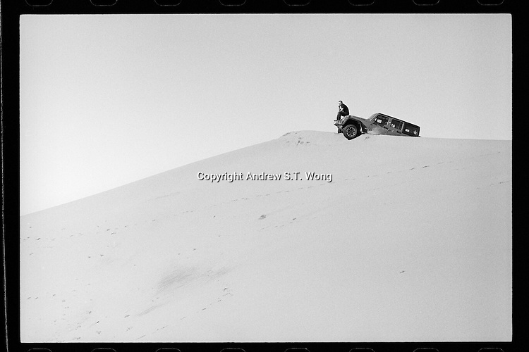 A Chinese driver sits on the bonnet of his Jeep on a sand dune in Tengger Desert, Inner Mongolia, China, July 2013.