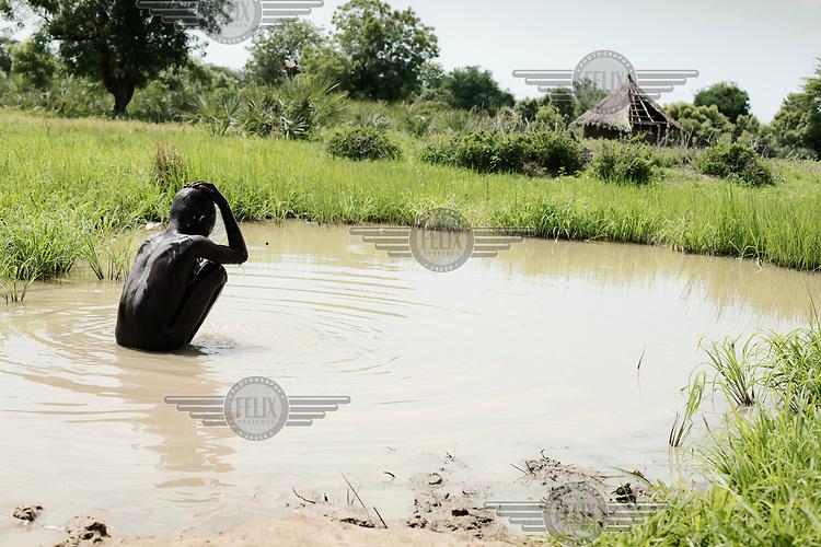 A boy bathing in a pool of water.