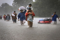Residents carrying young children and belongings escape rising flood waters caused by Hurricane Harvey in Houston, Texas, U.S.A. on August 28, 2017.
