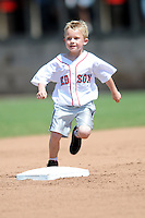 A young fan races Slugger, the mascot of the Portland Sea Dogs, during a game versus the Altoona Curve at Hadlock Field in Portland, Maine on June 2, 2013. (Ken Babbitt/Four Seam Images)